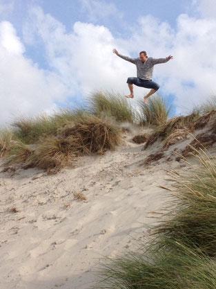 Mann springt von der Düne auf Ameland