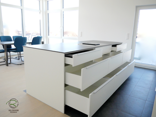 Inselküche mit Blum Legrabox mit geschlossenen SeitenwangenKücheninsel in weiß mit Keramik-Neolith Arbeitsplatte mit Highboard für Kühl-Gefirrschrank u. Backofen mit brauner, indirekt beleuchteter Nischenrückwand u. Aluminium Griffleiste auf der Front