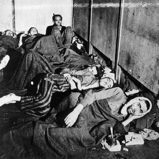 Befreite KZ-Häftling in einer Unterkunftsbaracke. Foto: unbekannt, nicht datiert (Mai 1945). Archiv KZ-Gedenkstätte Neuengamme DN 1983-2695