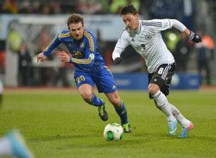 Mesut Özil im Duell mit dem Kasachen Konstantin Engel.  Bild: DPA