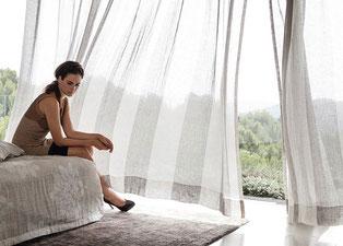 Frau sitzt auf dem Bett, die halbtransparente Gardine weht im Wind