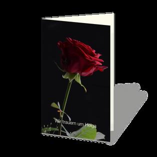 """Trauerkarte mit roter Rose auf schwarzem Hintergrund und der Text: """"Wir trauern um ..."""""""