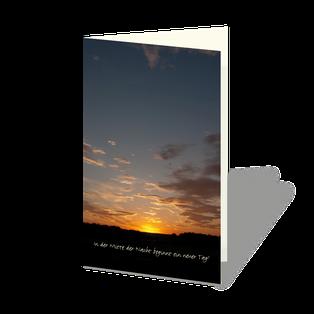 Trauerkarte mit Sonnenuntergang. Durch das Licht der untergehenden Sonne erleuchtete Wolken. Im Kontrast der fast schwarze Horizont, darin ein kleiner Vers.
