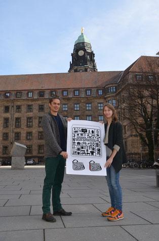 Der Dresdner Mario Süßbrich und die Hamburgerin Laura Mästele halten Ihren Entwurf, zur Ausschreibung der künstlerischen Gestaltung des Student Welcome Package 2017, in Ihren Händen.