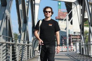Erdin ist mit einem Blindenstock, Notebook Tasche und Sonnenbrille unterwegs. Er läuft geradewegs auf die Kamera zu. Zu Sehen ist ein Teil einer Brücke auf der er sich befindet. Im Hintergrund der blaue Himmel, eine Baustelle und ein Gebäude.