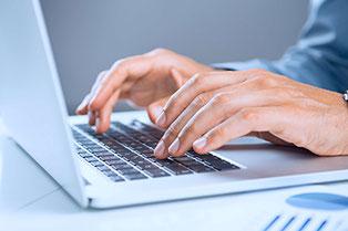 Mann, der auf einer PC-Tastatur etwas schreibt.