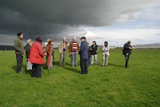 Abbildung: Klaus erzählt über die Zusammenhänge im Neolithikum zwischen Orkney und Südengland, im Hintergrund zieht ein Sturm heran / © Klaus Schindl