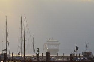 Dunst umhüllte Fähre beim Einlaufen in den Hafen, im Vordergrund Segelboote