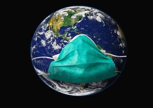 Die Welt in Zeiten des Corona-Virus: Weltkugel mit grüner Atemmaske