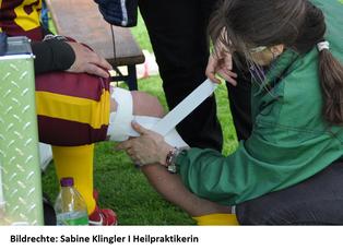 Tape-Verband am Spielfeldrand für eine akute Verletzung