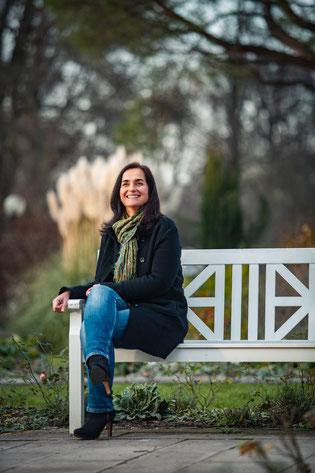 Foto von Iris Felder Frau ist glücklich und lacht auf Bank sitzend