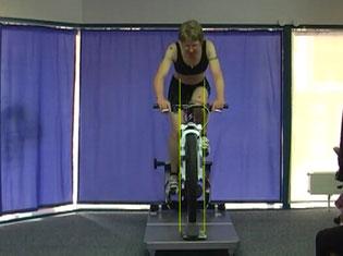 ein Radfahrer sitzt auf dem Bikefitting Drehteller, bleibt während der professionellen Überprüfung aus 4 Perspektiven sitzen, die Einstellung des Rades wird nach Auswertung optimiert, vorher-nachher dokumentiert