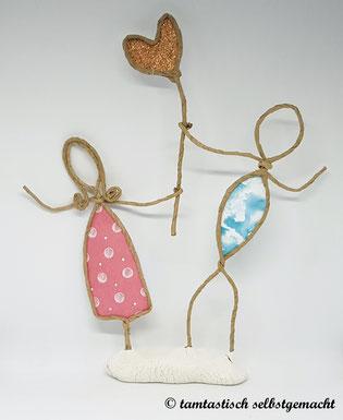 Papierdrahtfigur-Pärchen-Frau-und-Mann-halten-gemeinsam-ein-goldenes-Herz