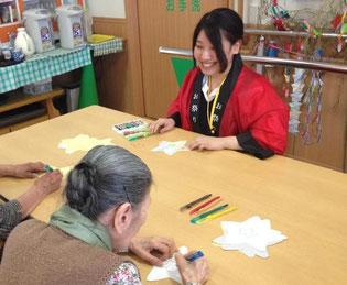 色ぬりの仕方を、おじいちゃんおばあちゃんたちに丁寧に教えています。