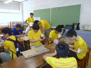 参加者が身に付ける鈴飾りを作っています。