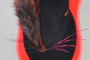Schwarzer Hase aus Filz mit einer Gesichtshälfte aus schwarz-rotem Fell