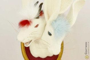 Gefilzter weißer Hase mit Dachsfell auf dem Kopf und grüner Kette