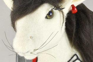 Weißer Hasenkopf aus Filz mit grünen Augen, roten Ohrringen und schwarzen Haaren zwischen den Ohren