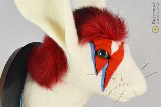 Hasenkopf aus weißen Filz mit roten Haaren und rotem Blitz im Gesicht (David Bowie)