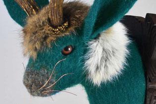 Trophäenkopf eines Hasen aus grünem Filz mit Rehgeweih