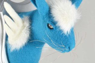 Blauer Hase aus Filz, mit weißen Flügeln und Fellflecken auf einem silbernen Trophäenbrett.