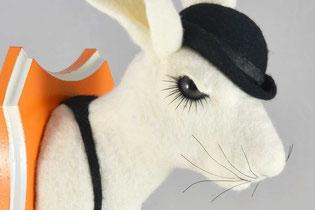 Hasenkopf aus weißen Filz mit schwarzen Hosenträgern und schwazer Meleone auf einem orange-weißen Trophäenbrett