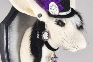 Kopf eines Hasen aus weißem Filz, mit schwarzer Mähne, schwarzen Hut und szenetypischen Schmuck.