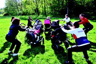 Eine Gruppe von Müttern stehen mit ihren Kinderwagen auf der Wiese. Dabei dient der Kinderwagen als Sportgerät.