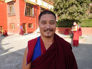 供物のミカンを配るチベット僧