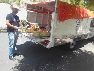 現地の特製オイスカトラックで、各家庭に配布・販売する野菜や果物を自ら運ぶマルティン会長