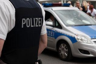 Ein Polizist und ein Streifenwagen.