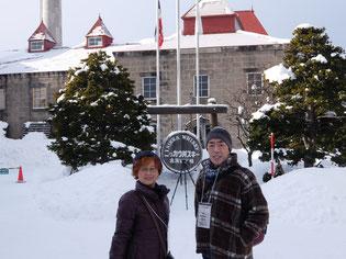 粉雪舞うニッカウイスキー余市蒸留所入口の前で