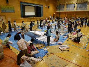 段ボールや新聞紙、エアセルマットを用いて、寝床の作成を行う児童たち。