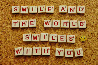 "Korkbrett mit aus Scrabble Buchstaben geformten Satz: ""Smile and the world smiles with you"""