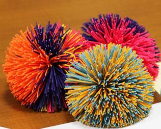 写真 「クッシュボール (Koosh Ball): カラフルなゴム紐が束ねられたようなボールのおもちゃ」