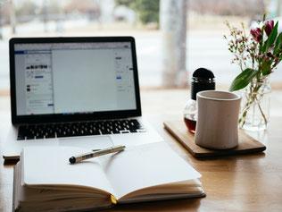 Auf einem Tisch mit Ausblick aus einem Fenster steht ein aufgeklappter  Laptop, davor ein Notizbuch mit Stift, eine Tasse Tee mit Honig und einer Vase mit kleinem Strauß.