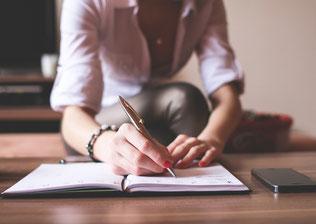 Eine Frau, von der man den Kopf nicht sieht, sitzt an einem Tisch und macht sich mit einem Kugelschreiber Notizen in eine Heft.