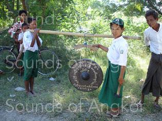 Gong processionnel birman. Il est suspendu au portant par un unique point d'attache, mais deux au niveau du gong. Au cours du jeu, la barre intermédiaire est maintenue par le musicien pour éviter l'oscillation de l'instrument.