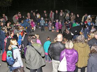 Laternenumzug im Kongresspark, wo sich die Kinder und alle Besucher im Kreis aufstellen und die Kinder Kipferl miteinander teilen.