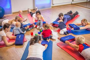 Eine Gruppe Mütter mit ihren Kindern liegen im Kreis. Die Mütter machen eine Sportübungen. Die Kinder spielen dabei.