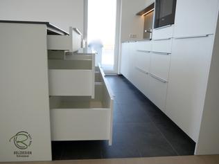 Weiße Küche mit Insel & Aluminium Griffleiste auf Front mit Schubladen, Kücheninsel in weiß mit Keramik-Neolith Arbeitsplatte mit Highboard für Kühl-Gefirrschrank u. Backofen mit brauner, indirekt beleuchteter Nischenrückwand, Kochinsel weiß