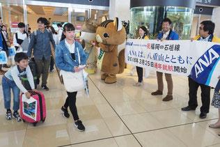横断幕を手に到着客を出迎える関係者ら=25日午後、南ぬ島石垣空港