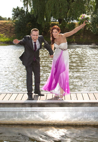 Hochzeitsaufnahme eines springenden Brautpaares , Hochzeit am Bootssteg, Achimer Bootshaus, lila farbiges Brautkleid, hochreißende Arme