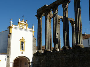 Säulen-Reste des römischen Diana-Tempels in Évora mit Kirche im Hintergrund vor blauem Himmel