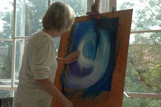 Een vrouw schildert met haar handen, met acrylverf in blauw met witte mengtinten