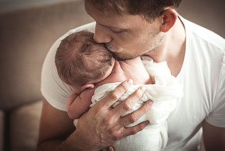 Newborn Baby wird geküsst festgehalten vom Papa im Arm festgehalten von der Familien Fotografin Monkeyjolie