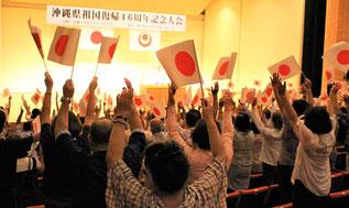 閉会前には、入り口で手渡された「日の丸」の旗を掲げ、聴衆が万歳三唱した=13日、豊見城市中央公民館