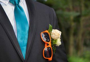 Farbaufnahme Bräutigam, orange Brille, Blume im Anzug steckend, starker Ausschnitt, Außenaufnahme