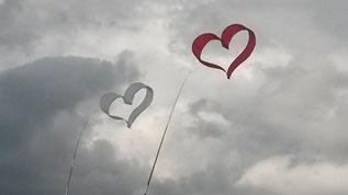 Zu sehen: wolkenbehangener Himmel. Vor dem Himmel Drachen in Herzform, die an einer Schnur steigen gelassen wurden.
