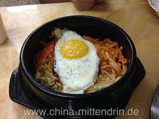 In einem koreanischen Restaurant in China bekommt man möglicherweise solch einen Reistopf. Natürlich isst man den komplett auf. Aber auch hier ist es üblich, den Anderen anzubieten zu probieren.